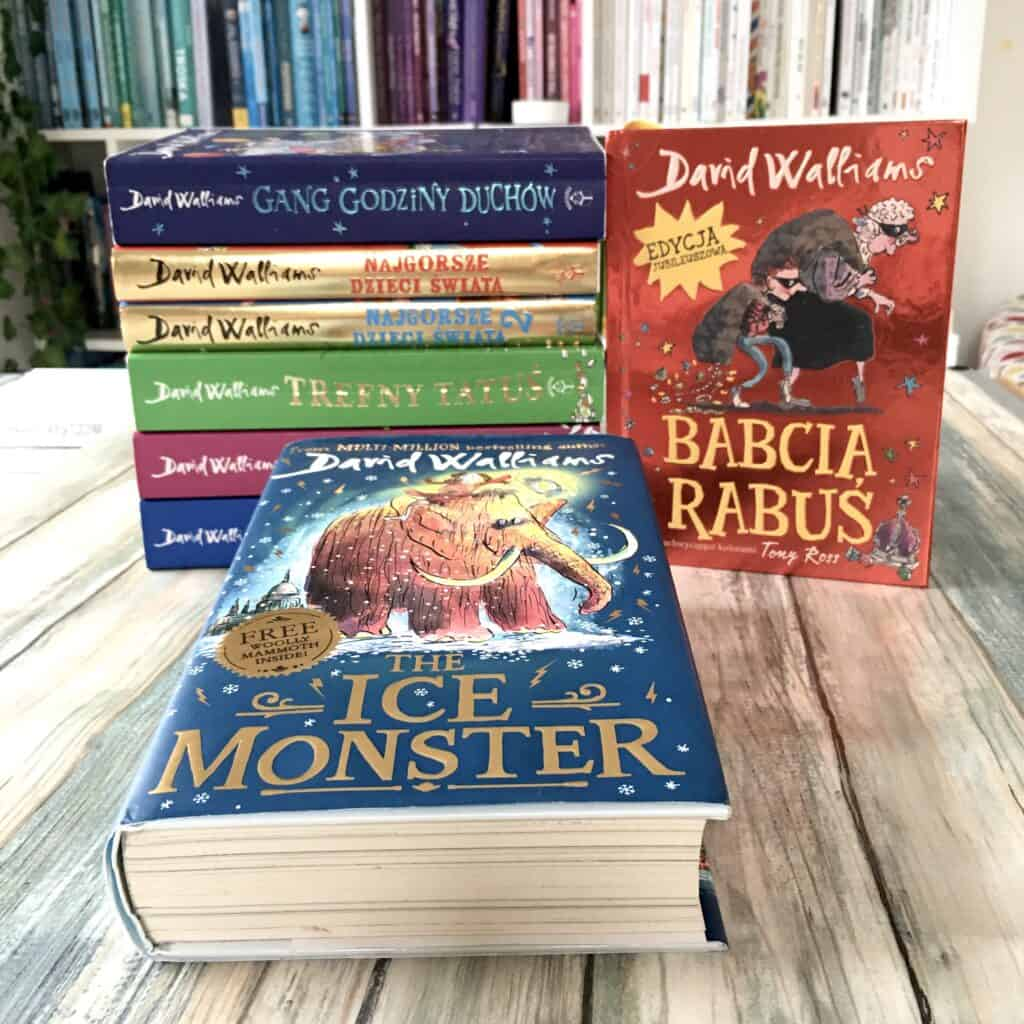 Książki Dawida Walliamsa są grube, aleteż czyta się je migiem. Idealne dla wszystkich, którymzczytaniem niekoniecznie podrodze, bo autor wjakiś magiczny sposób wie, jak pisać, żebydzieci czuły te konkretne opowieści. Moja córka kiedyś powiedziała, żejak się czyta te książki, tosię ma wrażenie, żerodzice najchętniej byzakazali ich czytania. Bardzo trafna opinia, wielu rodziców zresztą nieprzepada zatwórczością tego autora, porównując dowygłupów Koszmarnego karolka.  Poniekąd może topoczucie humoru gdzieś się przecina zkarolkowym, aleksiążki Davida Walliamsa są owiele głębsze, najczęściej przemycają podtym płaszczycie humoru niezmiernie ważne tematy: nierówność społeczna, bida, bezdomność, trudne relacje wrodzinach itownajróżniejszych konfiguracjach.  Wybrał drogę przerysowywania postaci, żebytym zwrócić naszą uwagę napewne zachowania czycechy. Uwielbiam ten język itopoczucie humoru. Ojego wszystkich książkach pisałam niezliczoną ilość recenzji, bo bardzo kibicuję wydawcy, któryzdecydowała się tę nieco kontrowersyjną literaturę wprowadzić nanasz rynek.  Nazdjęciu najnowsza część. Kiedy topiszę, on jest jeszcze wdrukarni, dlatego pokazuję Ich Monster wwersji angielskiej. Już jednak trwa przedsprzedaż, bo plan jest taki, żeksiążek będzie wgrudniu wWaszych rękach.  Ajeśli nieznacie Davida Walliamasa, proponuję zacząć odBabci Rabuś, wktórejświetnie imomentami wzruszająco pokazana jest więź między wnukiem iwłaśnie babcią. Napoczątku chłopiec kompletnie niema ochoty spędzać znią czasu. Nieuważa, żebymieli wspólne tematy. Okazuje się, żebabcia potrafi zaskoczyć!